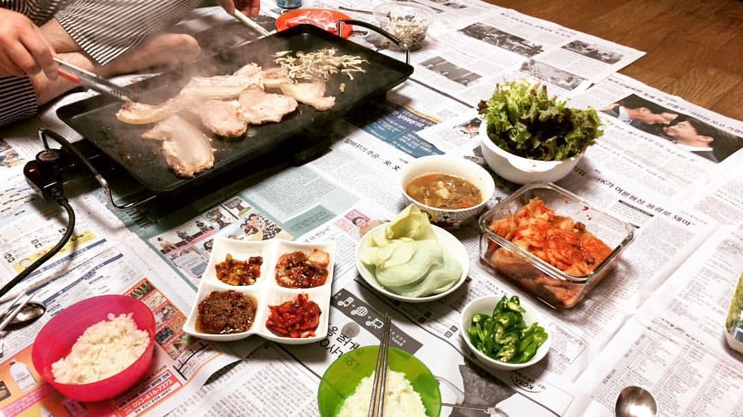 신문지를 깔고 고기를 구워먹는 사진